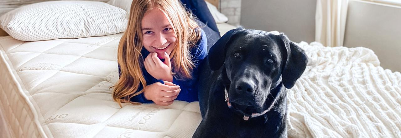 girl and dog on naturepedic chorus organic mattress