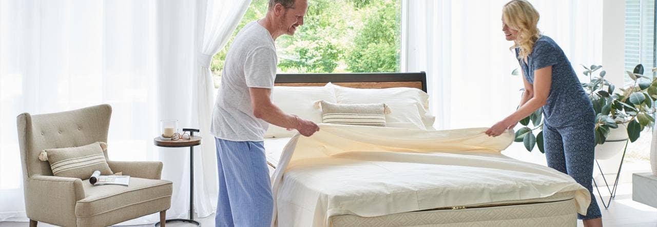 couple changing sheets on naturepedic halcyon arcadia organic mattress