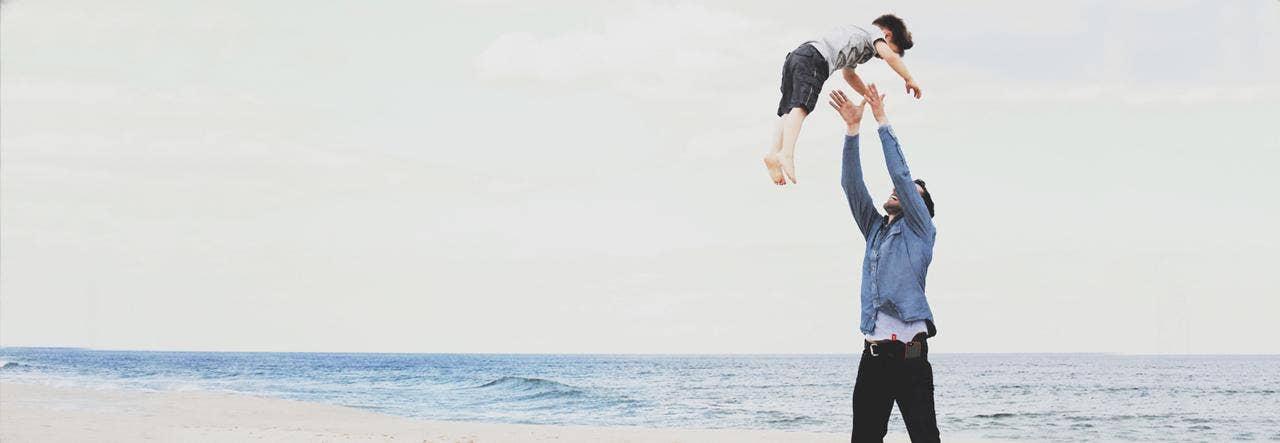 man throwing son in air at beach