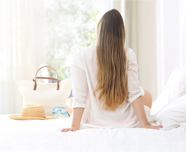 Woman with long hair sitting on bed facing window