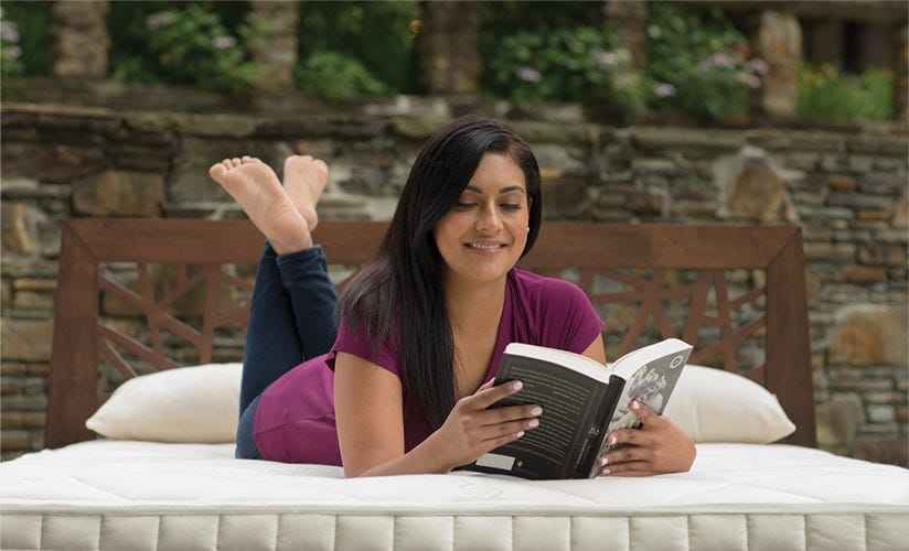 Woman reading book in bed in outdoor setting
