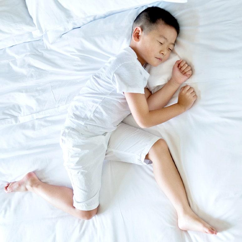 Boy sleeping on mattress