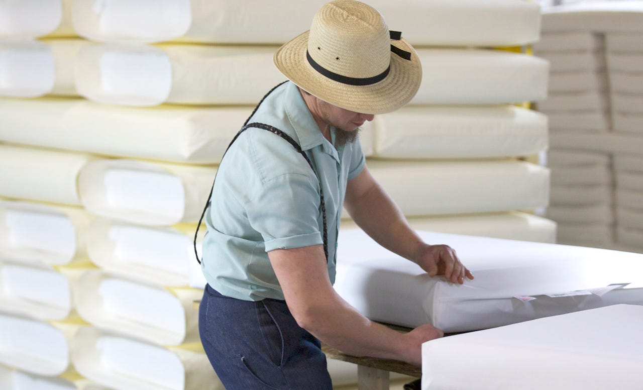 Amish worker inspecting mattress corner