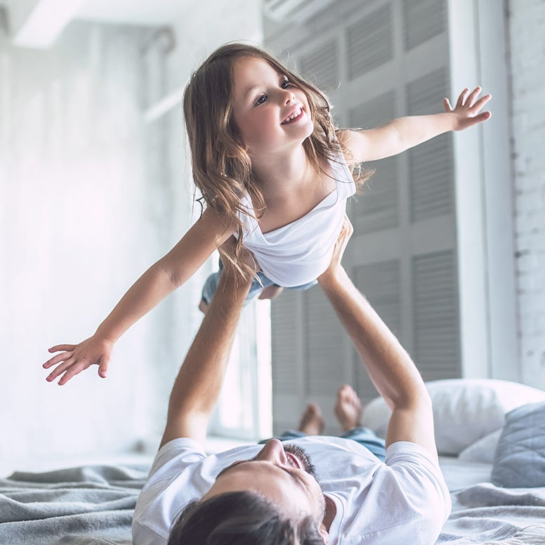 Father laying in bed holding up daughter in flying position