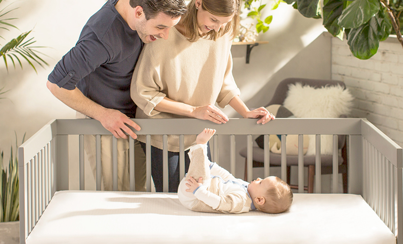 Mom and dad smiling at baby in crib