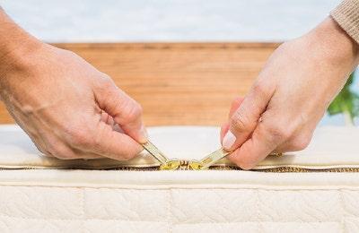 Couple holding zipper pulls after assembling EOS mattress