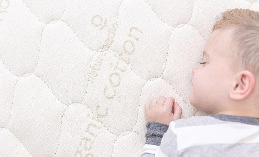 Close-up of child sleeping on mattress