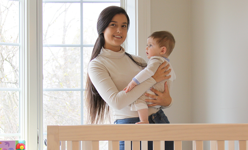 Mom holding young baby boy next to crib