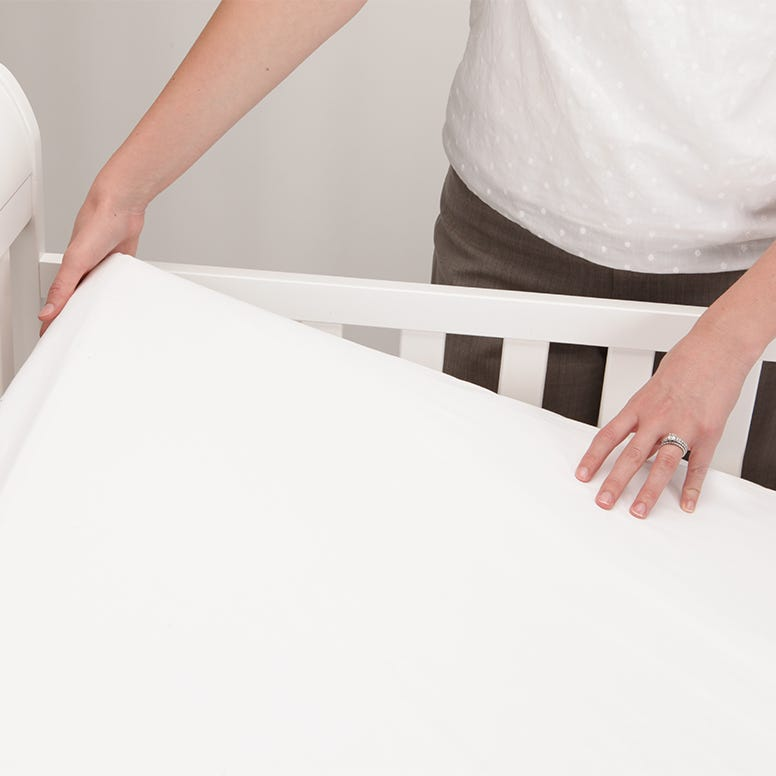 Mom holding up crib mattress corner in crib demonstrating firmness and a snug fit