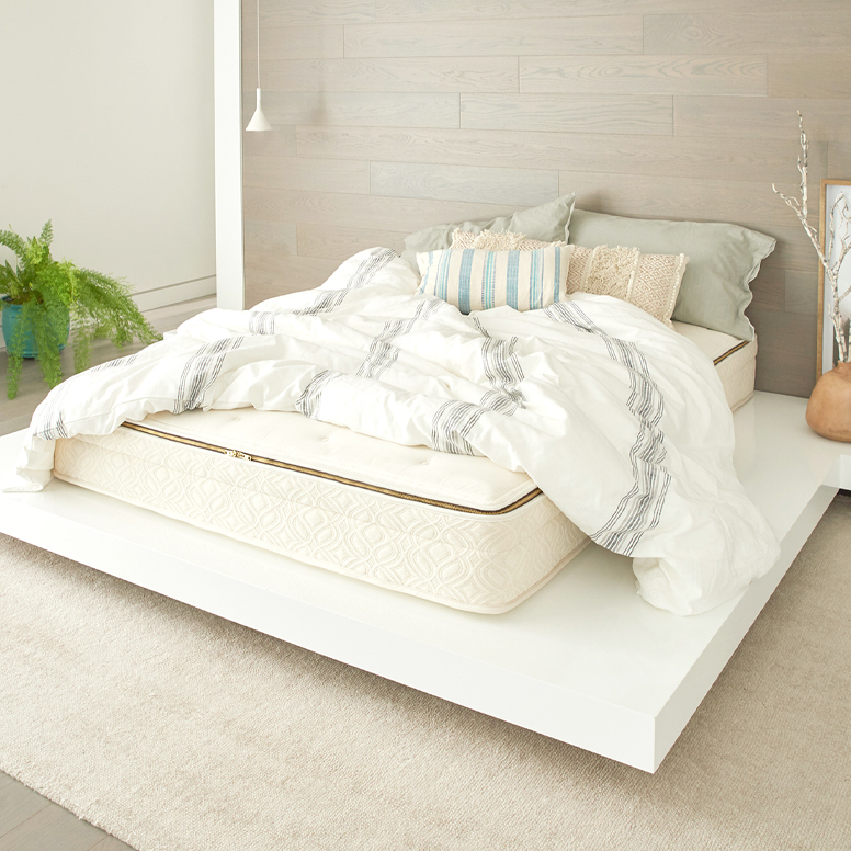 Luxury queen mattress in bedroom with pillows and blanket