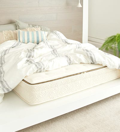Angled shot of Azure mattress with blankets pulled back