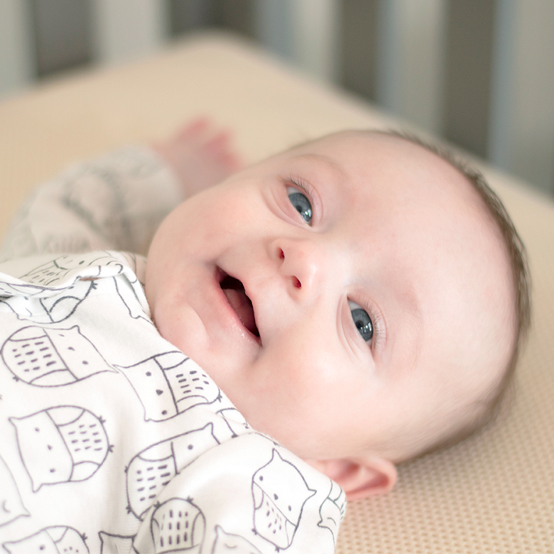 Close-up of baby laying on breathable crib mattress smiling
