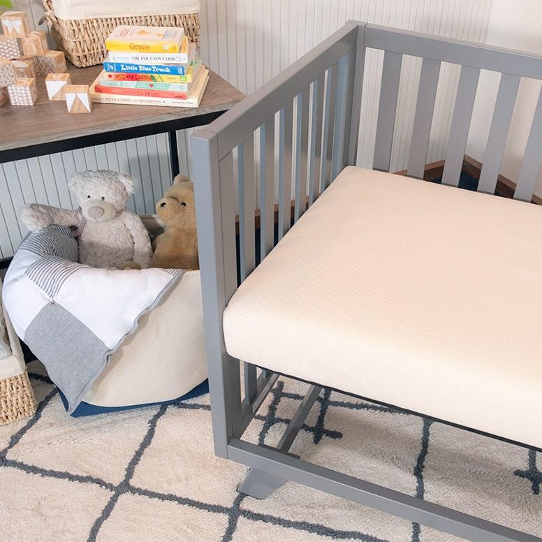 Crib mattress in grey crib in nursery setting