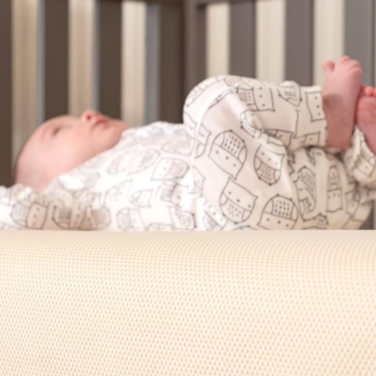 Baby laying on back on breathable crib mattress