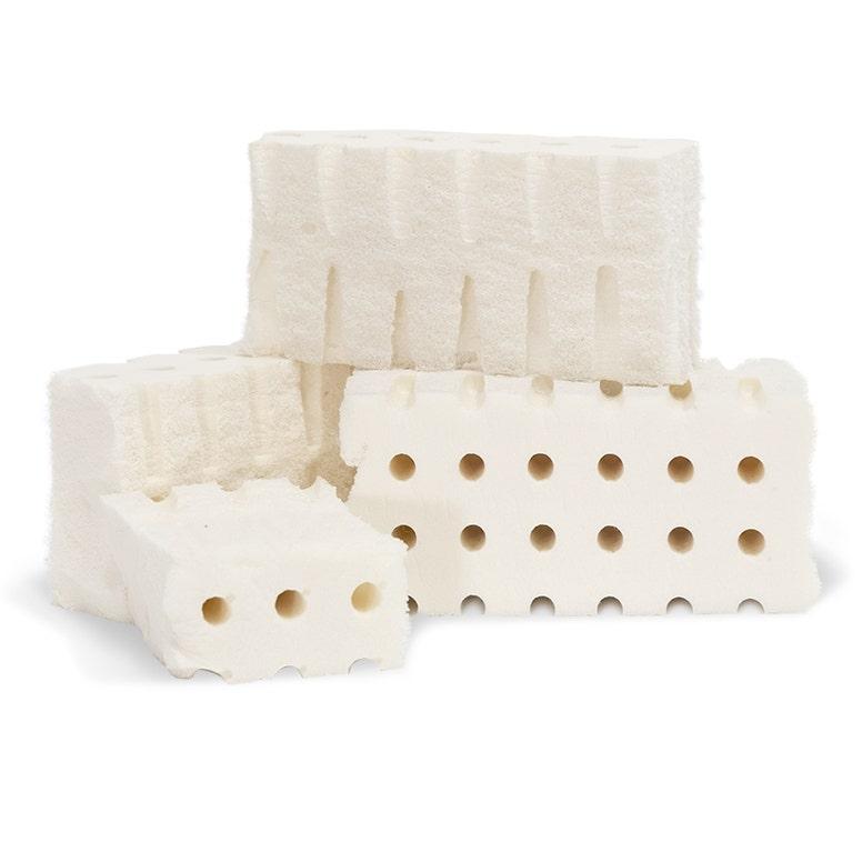 Stacked chunks of organic latex foam on white background